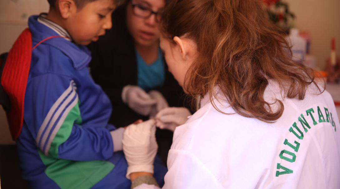 A high school student doing a summer medical internship abroad in Peru checks a child's blood sugar levels.